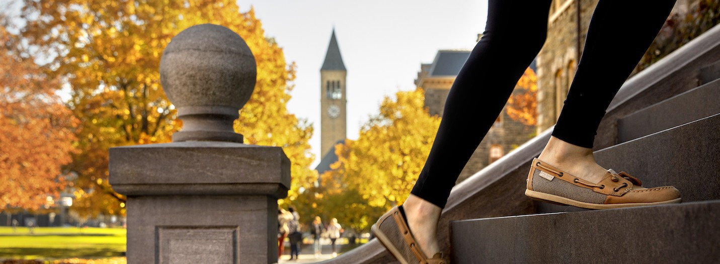 closeup of a person's feet walking up McGraw Hall steps with Clock tower in background