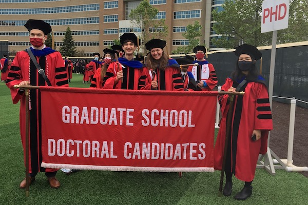 Eudes Lopes standing with group of graduates at commencement